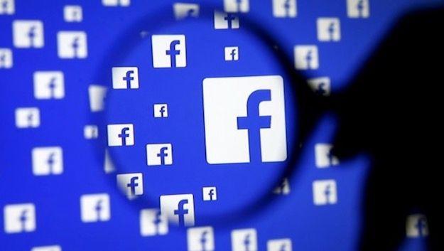 Foto che mostra il logo di Facebook sotto una lente d'ingrandimento