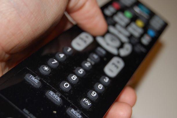 Foto che mostra un uomo che usa un telecomando universale