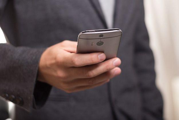 Foto di un uomo che usa uno smartphone HTC