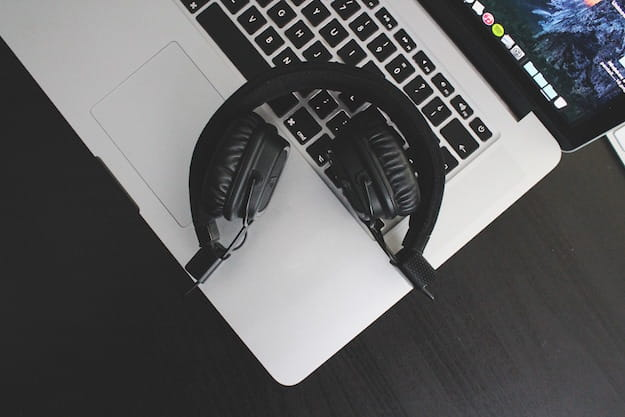 Foto di un Macbook e di un paio di cuffie