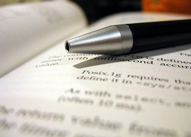 Foto che mostra una penna e dei fogli stampati