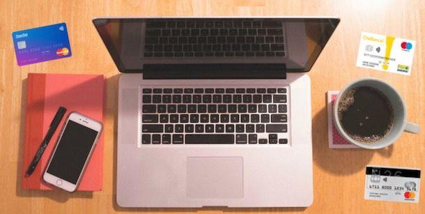 Foto di un computer e alcune carte di pagamento